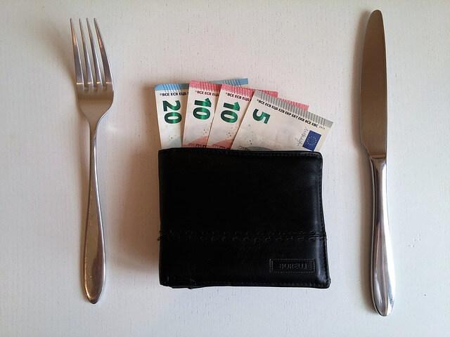 Gefüllter Geldbeutel zwischen Messer und Gabel