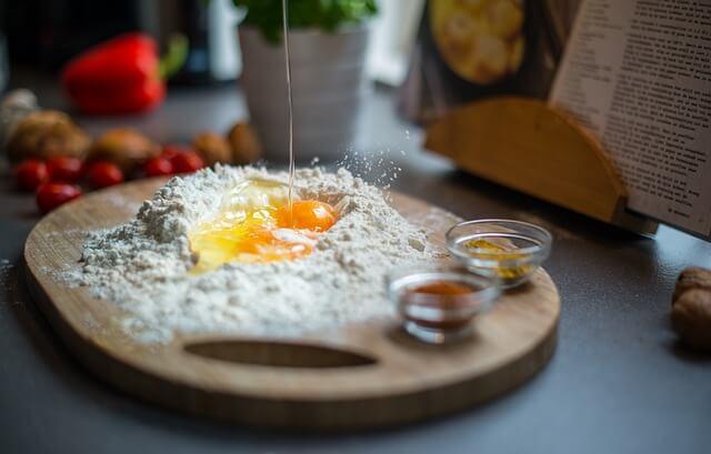 Ein aufgeschlagenes Ei in Mehlmulde mit Kochbuch im Hintergrund
