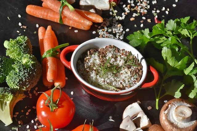 Ein Reistopf mit Karotten, Tomaten, Brokkoli, Pilzen und Kräutern rund herum