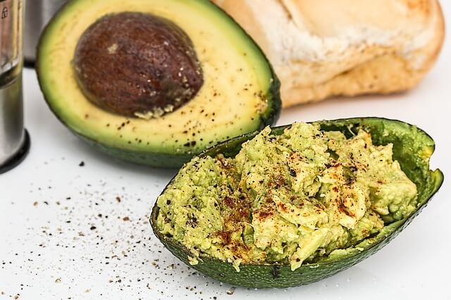 Eine aufgeschnittene Avocado mit Creme und Brot im Hintergrund