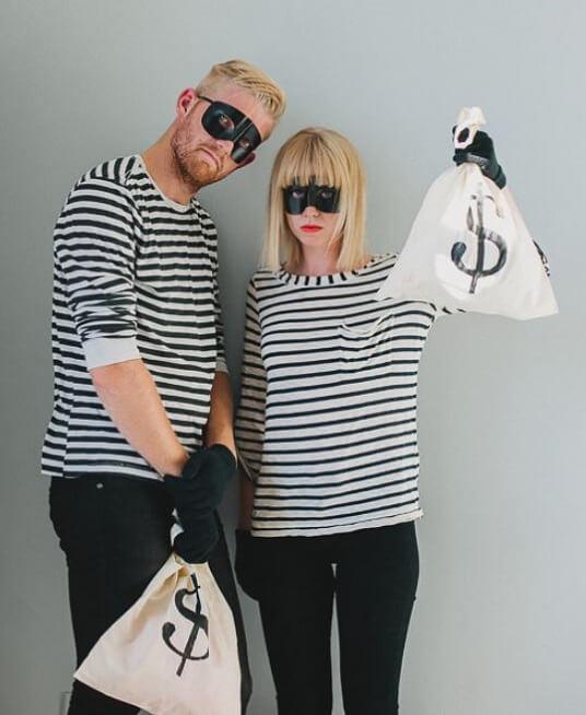 DIY-Kostüm für Karneval, Halloween oder Fasching. Mann und Frau in Bankräuber-Kostüm mit gestreiften Oberteilen, schwarzen Masken und Beuteln voll Geld