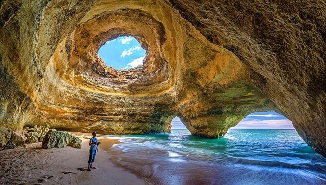 Mensch in einer Felshöhle im Meer in Portugal, die durch ein Loch an der Oberseite erleuchtet wird