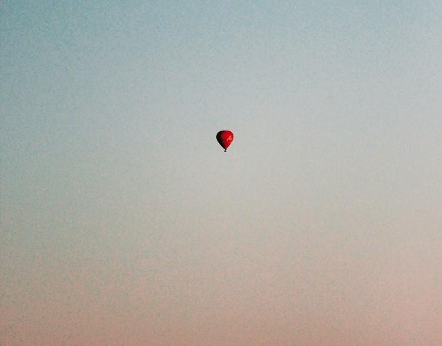 Roter Heißluftballon in der Ferne auf einem leicht rot gefärbten Himmel