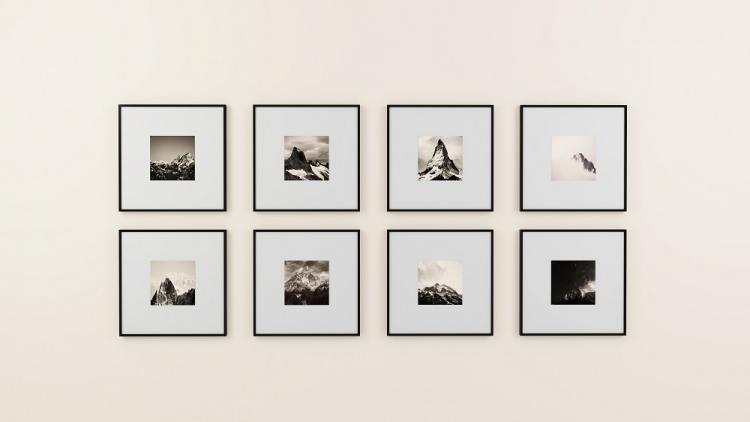 Helle Wand mit wenigen geordneten gerahmten Fotos