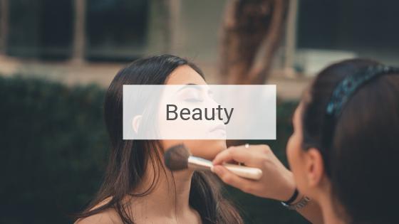 Junge Frau, die von ihrer Freundin geschminkt wird