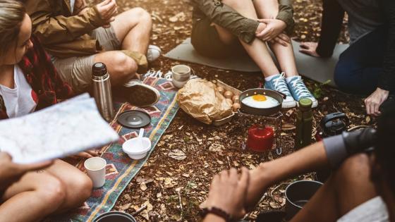 Eine Gruppe von Freunden, die auf dem Waldboden Campen und essen