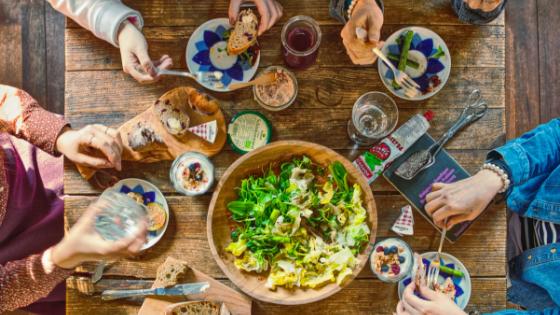 Esstisch mit Salat, Brot und Dips aus der Vogelperspektive mit Freunden, die am Tisch sitzen und essen