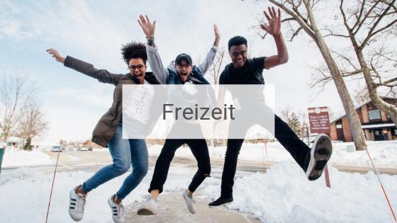 Drei Freunde im Schnee, die jubelnd in die Luft springen