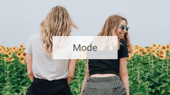 Zwei junge Frauen in modischer Kleidung sitzen lachend vor einem Sonnenblumenfeld