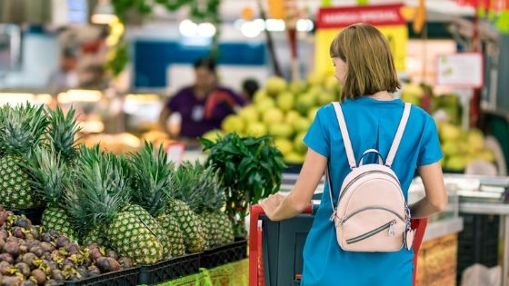 Frau mit Einkaufswagen im Supermarkt vergleicht Preise beim Einkaufen