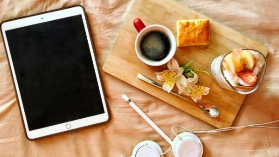 Kaffee und Snack neben Tablet