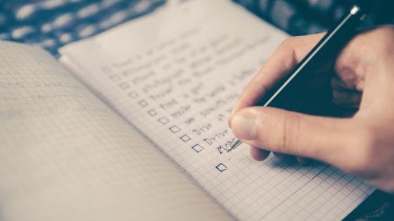Hand schreibt Einkaufsliste in Notizbuch
