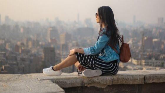 Modische Frau sitzt auf Mauer und sieht in die Ferne