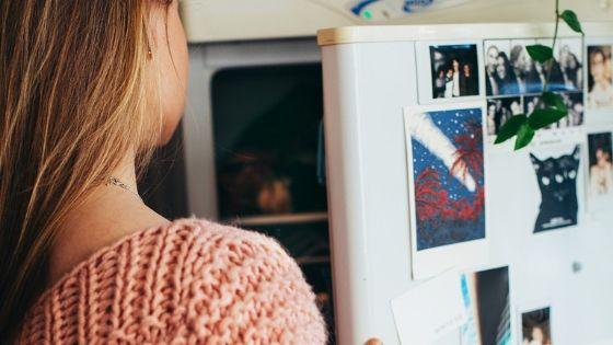 Junge Frau organisiert Lebensmittel im Kühlschrank, damit nichts verdirbt und neu gekauft werden muss