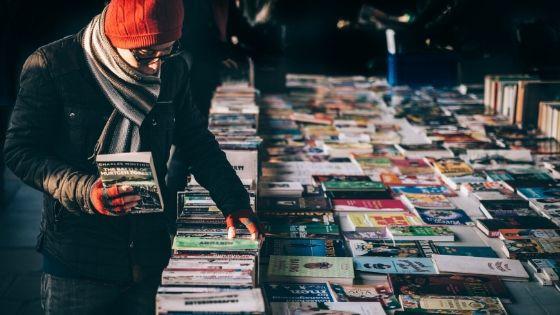Mann stöbert auf dem Flohmarkt nach günstigen, gebrauchten Büchern