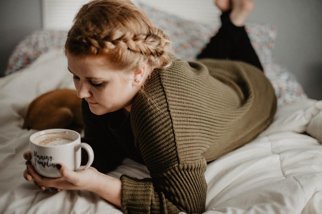 Femme rousse en pull vert allongée sur son lit avec un mug