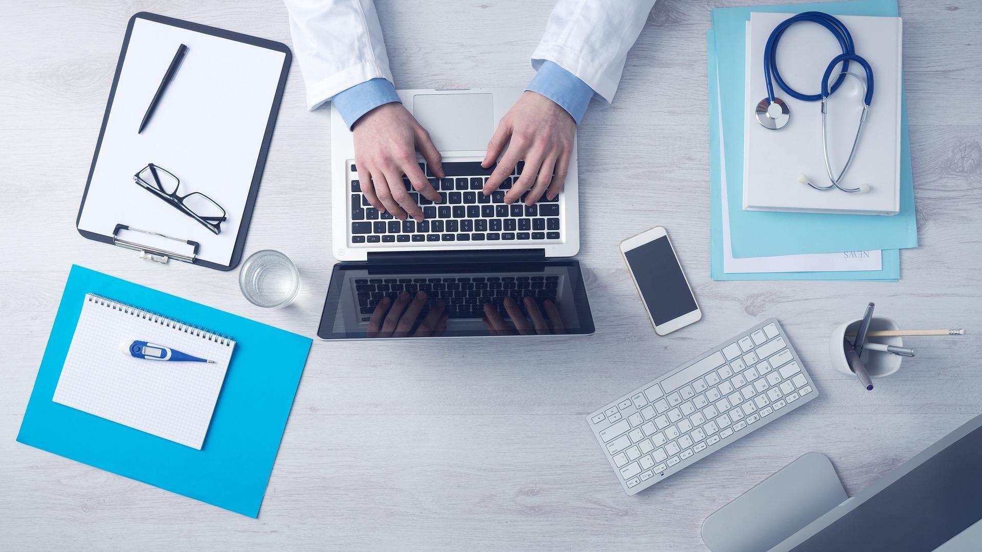 Mains de médecin sur un ordinateur avec lunettes, stethoscope, crayon, termomètre et blocs notes