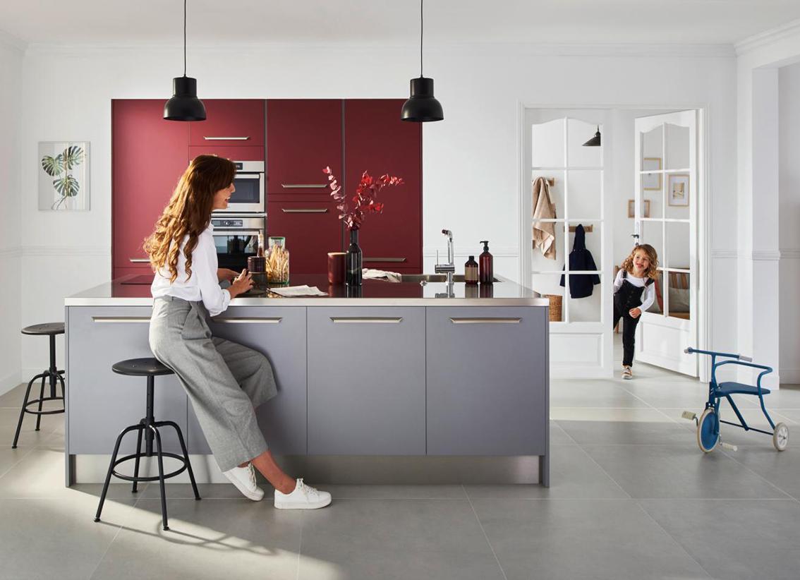 Femme assise dans une cuisine Lapeyre grise et rouge avec une petite fille