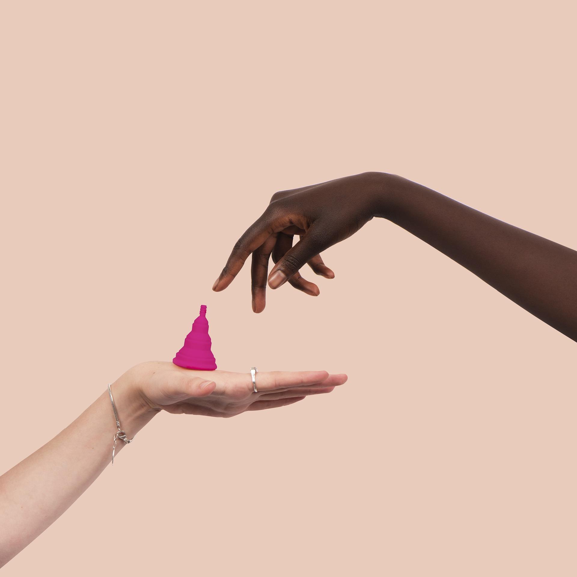 Deux mains échangeant une coupe menstruelle rose sur fond beige