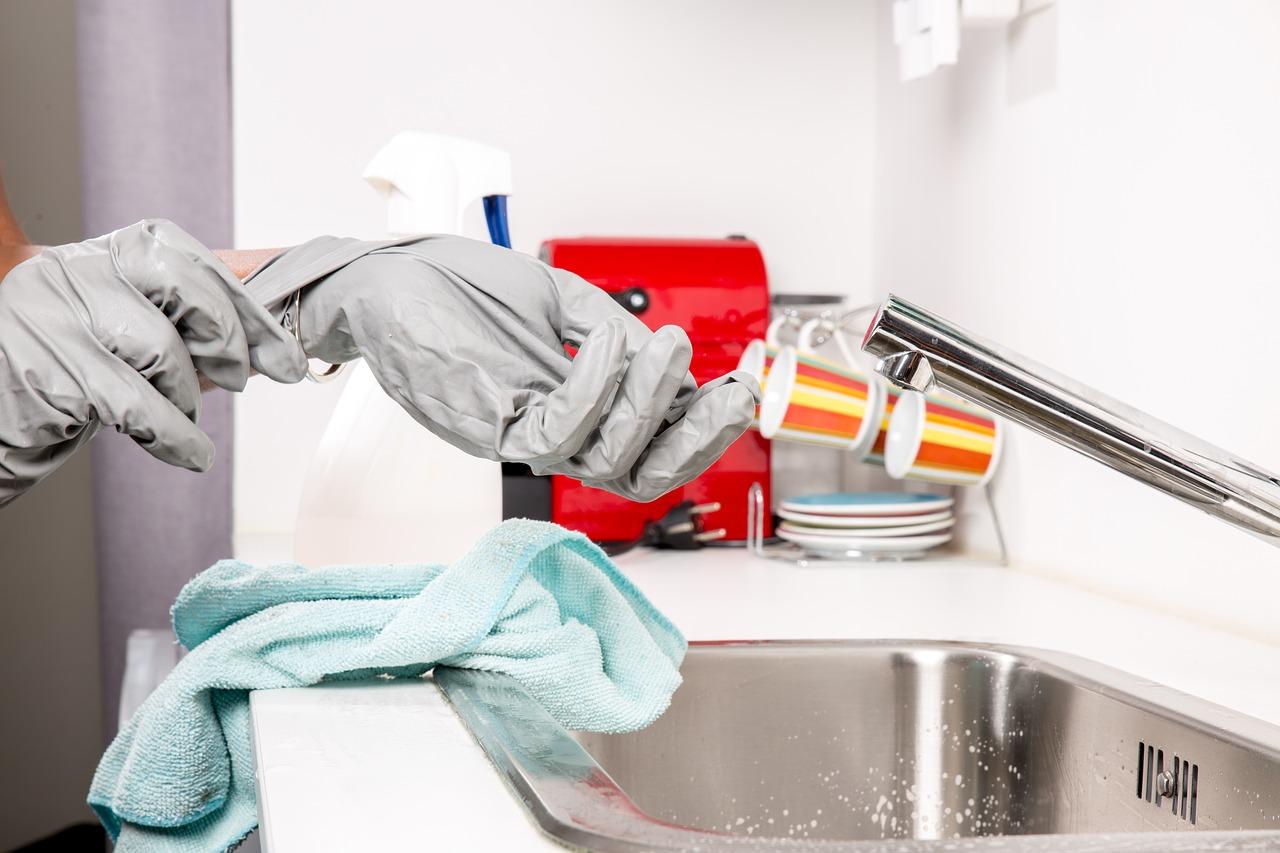 Personne qui enlève ses gants de cuisine gris devant un évier avec un chiffon bleu