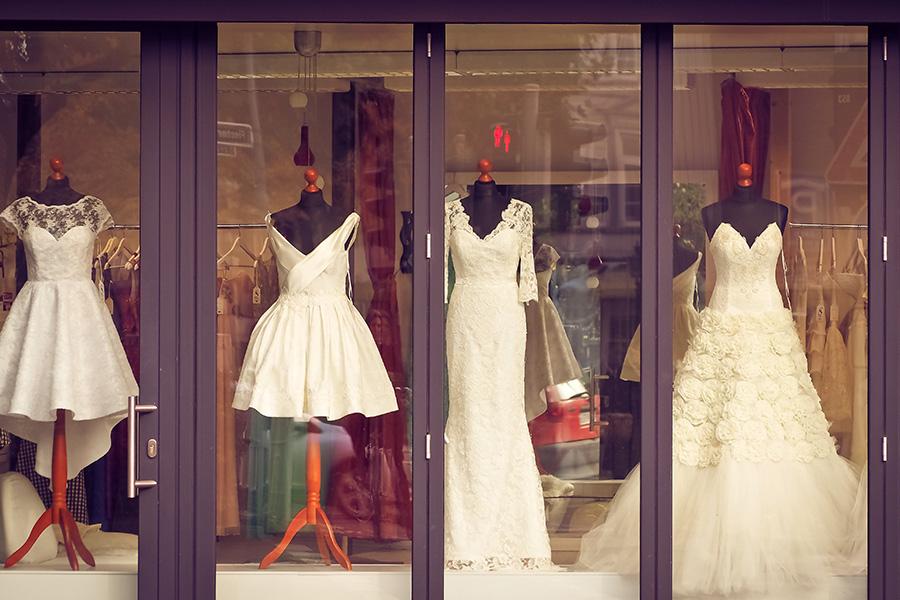 Vitrine de magasin de mariage avec quatre robes de mariées sur des mannequins noir