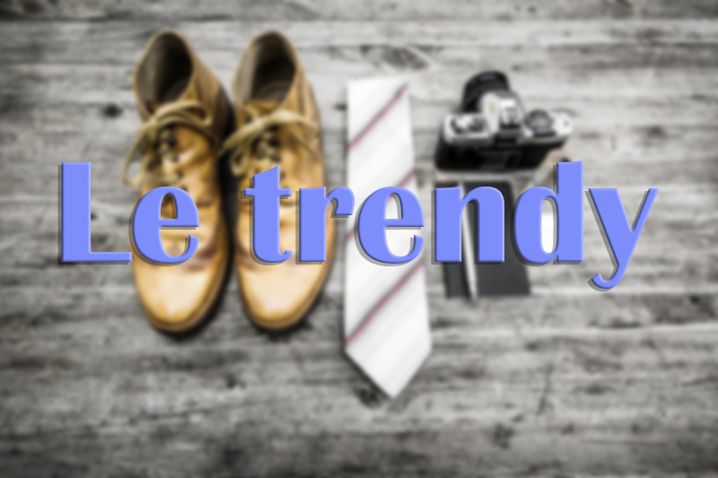 """Boots, cravatte et appareil photo sur parquet avec titre """"Le trendy"""""""