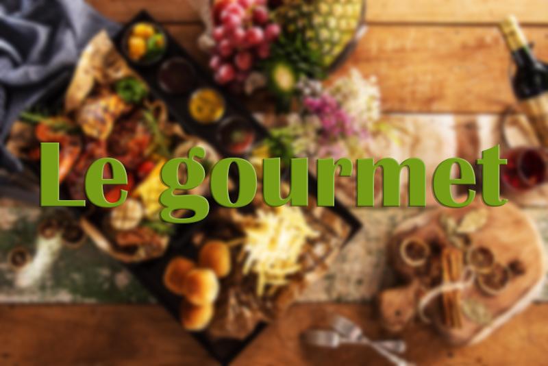 """Table en bois avec différents aliments et plats et titre """"Le gourmet"""""""