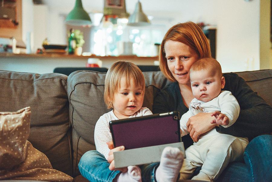 Femme sur un canapé avec deux enfants qui regardent une tablette