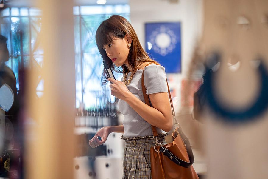 Femme dans une boutique qui sent un parfum