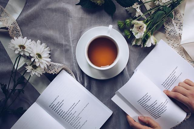 Livres ouverts sur une table avec fleurs et tasse de thé