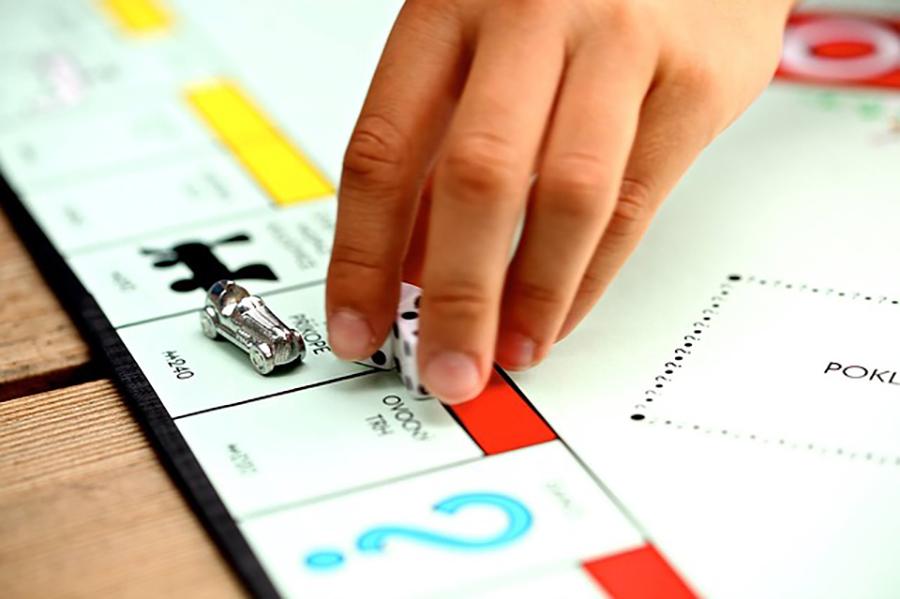 Plateau de Monopoly avec une main qui ramasse des dés