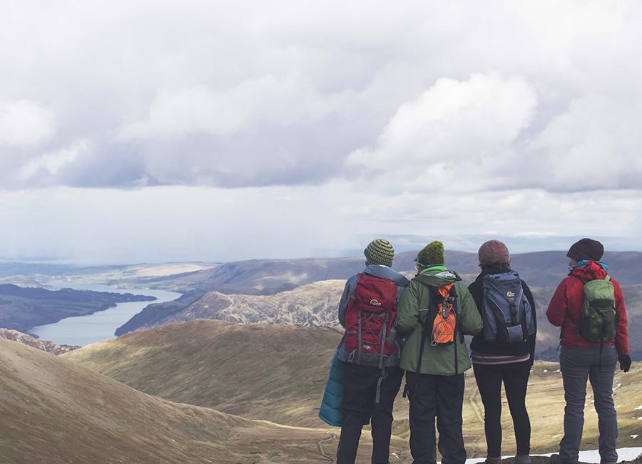 Quatre amis en montagne qui observent la vue