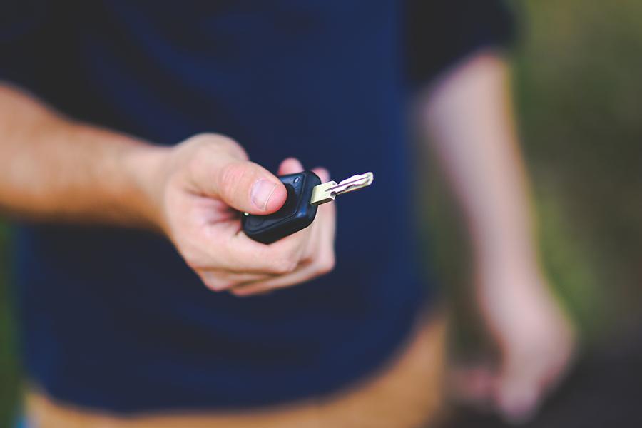 Homme en polo bleu avec clés de voiture
