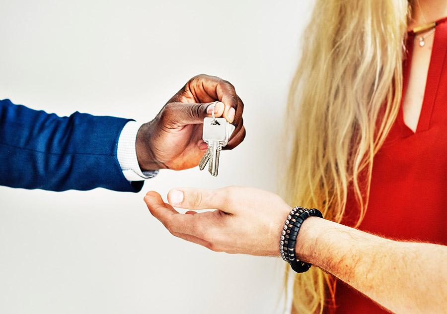 Personne qui donne des clés de maison à un couple