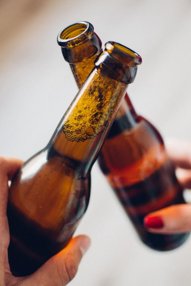 Two people drinking beer bottles