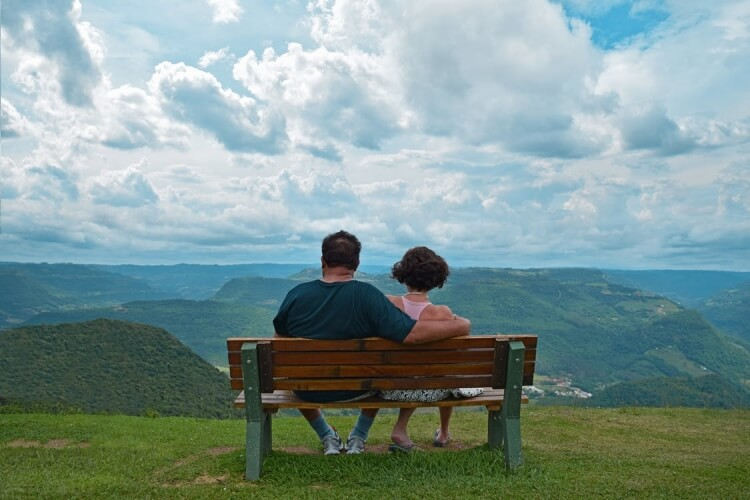 couple sat on park bench looking at the view