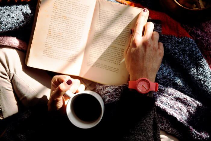 Woman reading with a coffee and blanket