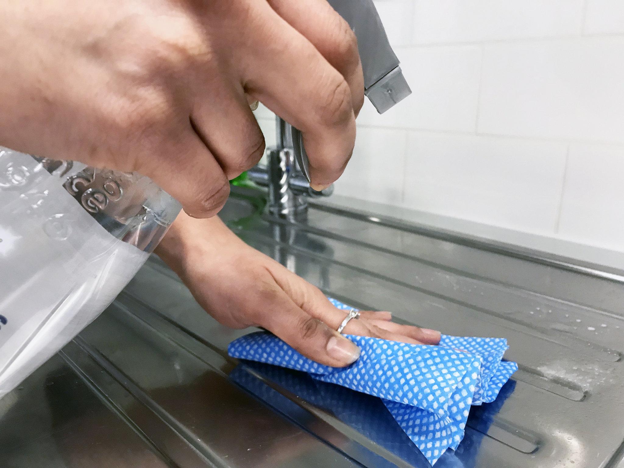 Woman using white vinegar spray to clean kitchen