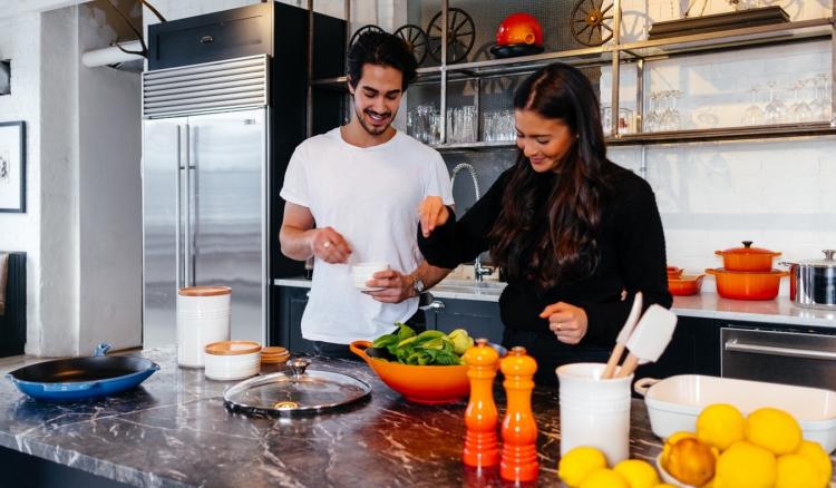 couple making fresh salad in kitchen