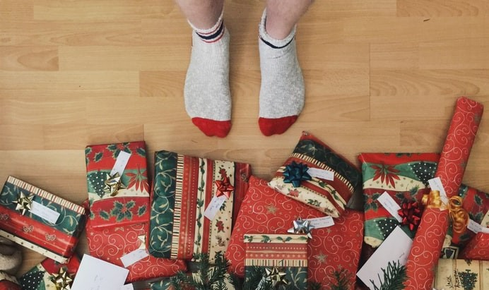 person standing in front of wrapped christmas gifts