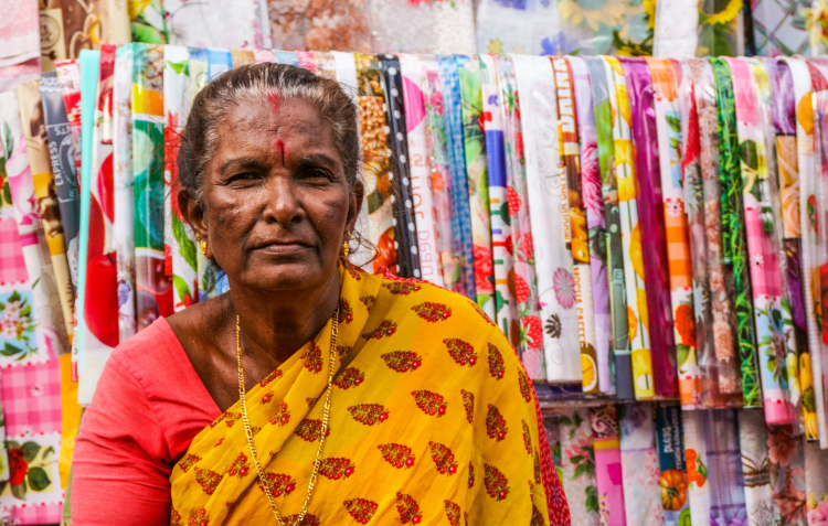 woman standing in front of colourful textiles